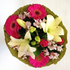 Bouquet of lilies, roses and gerberas in a lotus wrap.
