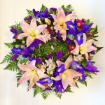 Wreath of pink lilies and iris with seasonal blooms.