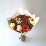 This beautiful lush bouquet is full of Christmas cheer in a mix of stunning reds, whites and green tones.