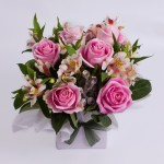 Box arrangement of roses and alstroemeria.