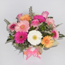 Gerberas and roses in delicate pastel shades.