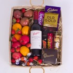 Hamper of mixed fruits, milk and dark chocolates and a bottle of wine.