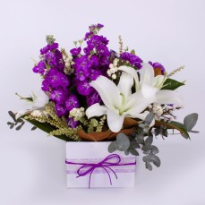 Box arrangement of purple and white flowers