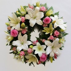 Delicate wreath of lilies and roses in pinks and whites.