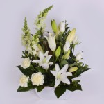 White seasonal flowers, including Oriental lilies, roses and carnations, in a ceramic pot.
